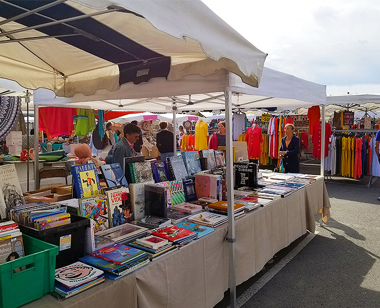 Books and clothing for sale in the Cap Ferret market.